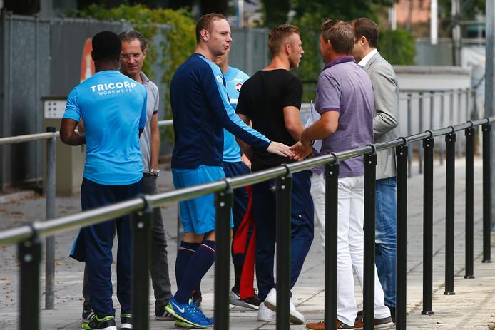 Elmo Lieftink (blauwe schoenen) in gesprek met Roland Vroomans.