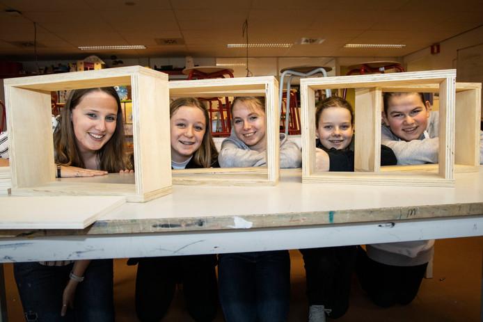 Docente Suzanne Härle (links) en vier van haar leerlingen bouwen een drijvend kunstwerk met 21 bewegende fotokasten.