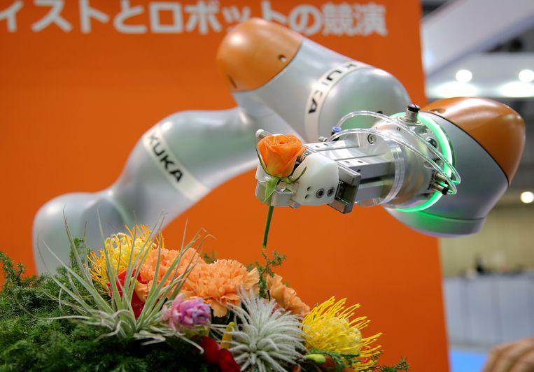Een bloemschikkende Kuka-robot. De indruk bestaat dat aankopen van dit soort hightech gecoördineerd worden door de Chinese overheid. Beeld AP
