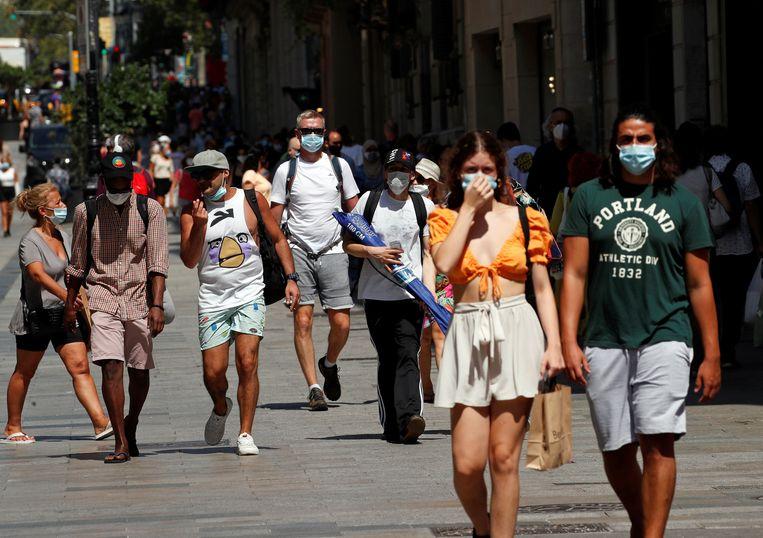 Mensen op straat in Barcelona, waar het reisadvies is aangescherpt van geel naar oranje.  Beeld REUTERS