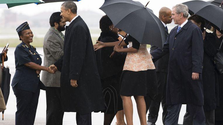 President Obama, Michelle Obama (onder paraplu) en George W. Bush bij aankomst op Waterkloof Air Base vliegveld in Zuid-Afrika. Beeld ap
