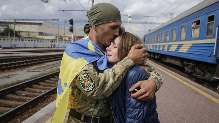 Een uit dienst ontslagen Oekraïense militair omhelst zijn vriendin na aankomst in Kiev. Beeld epa