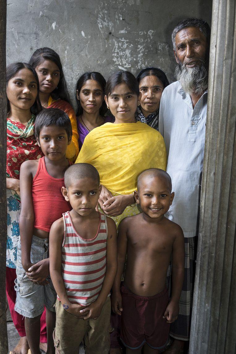 Shefaly (18, midden, werkt al zes jaar) en haar zusje Shiuly (20, links) verdienen het geld voor deze familie in Gazipur, samen 140 euro per maand. Beeld catrien ariens