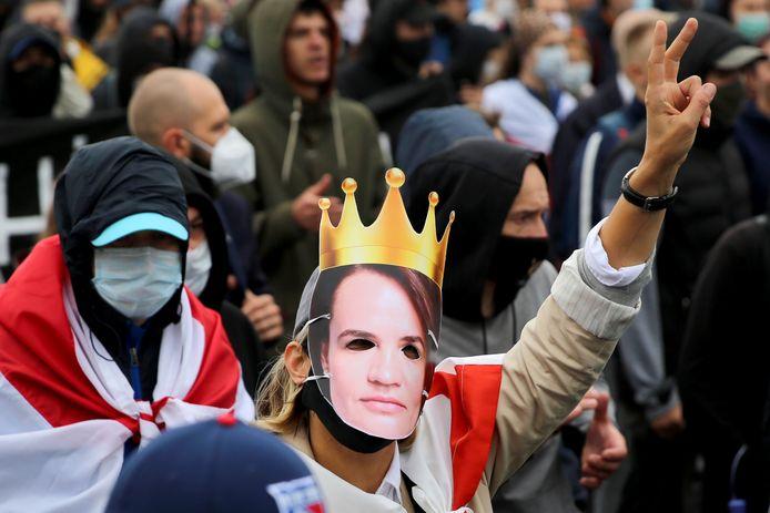 Een protestant draagt een masker van oppositieleidster Svetlana Tichanovskaja.