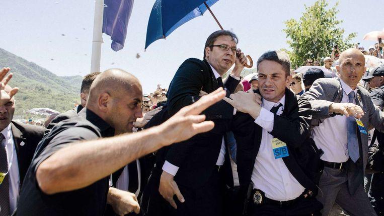 De Servische premier Aleksandar Vucic (bril) wordt weggevoerd nadat hij door een boze menigte is belaagd. Beeld null