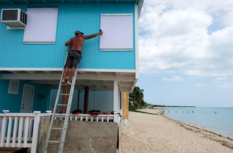 Een man spijkert de ramen van een strandhuis in Puerto Rico dicht.