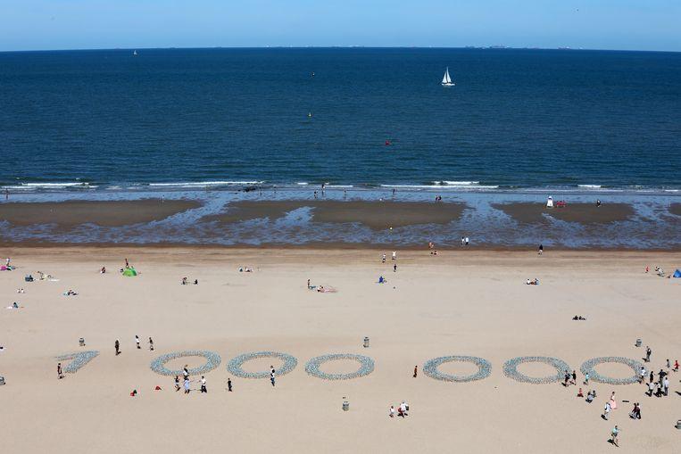 Het feit dat een miljoen gezinnnen elektriciteit kan krijgen vanaf de windmolens op zee werd op het strand van Oostende uitgebeeld met mini-windmolens.