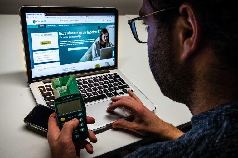 Een man aan het internetbankieren met ABN Amro. Het telebankieren van de Nederlandse bank kampte met een storing door een DDoS-aanval.