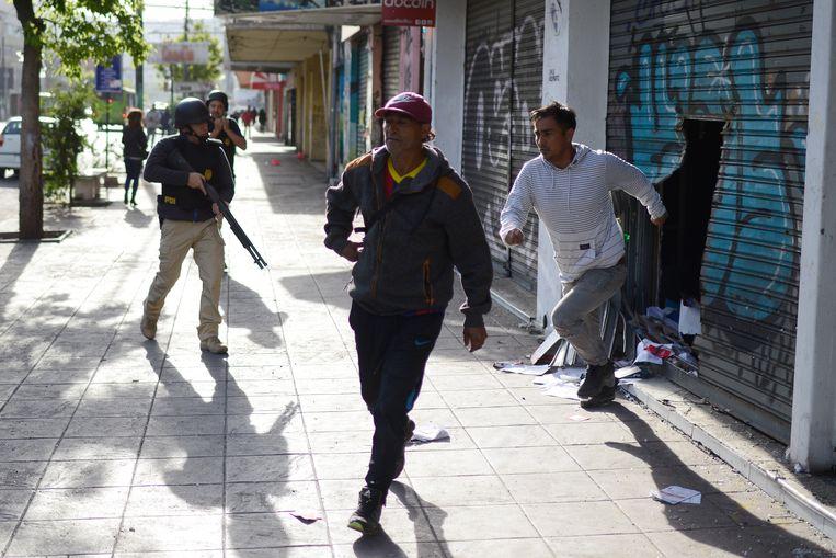Demonstranten rennen uit een geplunderde winkel in Valparaiso, Chili. Beeld null