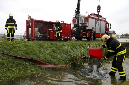Brandweermannen voeren het overtollige water af met pompen in De Lier in het Westland.