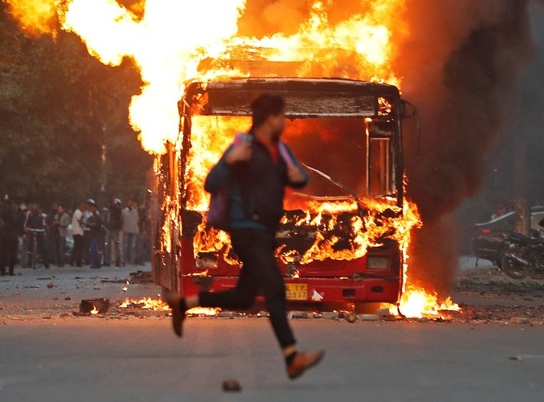 Een man rent langs een bus die in brand is gestoken uit protest tegen de wet.  Beeld REUTERS
