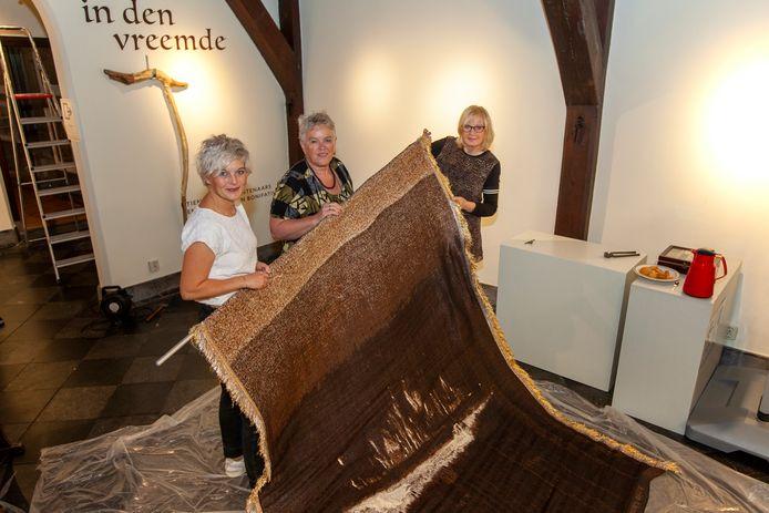 De conservatoren Stephanie Rompa en Teatske de Jong  en kunstenares Anke Land tijdens het inrichten van de expositie 'in den vreemde' in Stadsmuseum Woerden