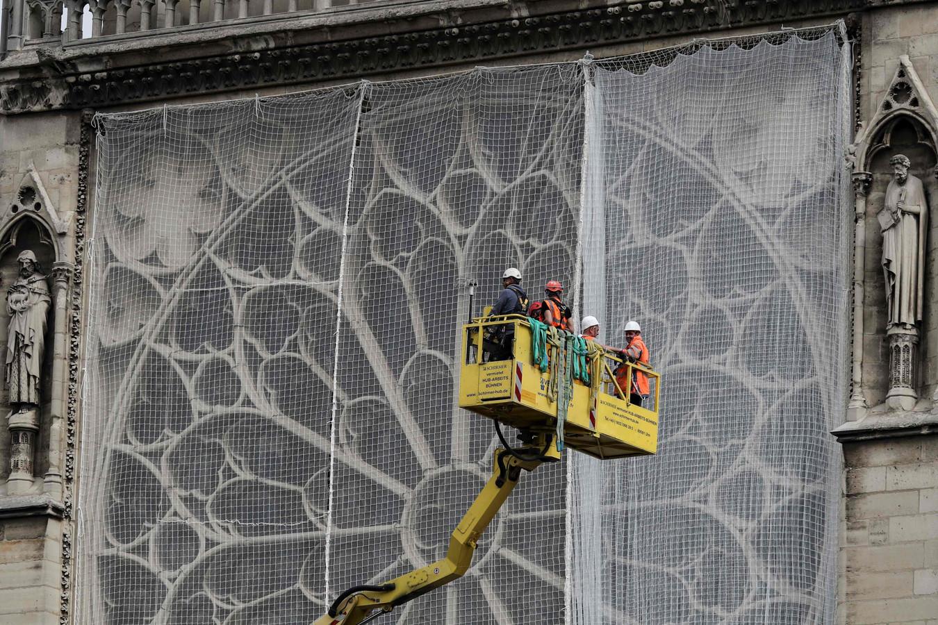Voor de glasvensters worden netten gemonteerd.