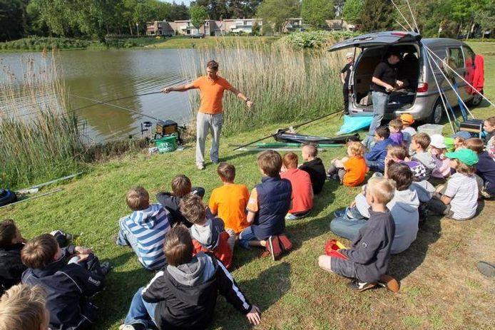 Theo Lucius (oranje shirt) geeft een visclinic in Son in 2011.\n