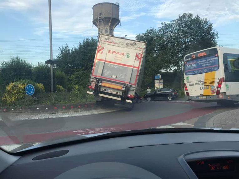 De vrachtwagen kwam vast te staan op de verhoogde berm van de rotonde.