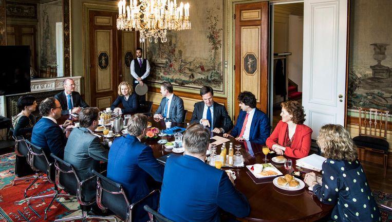 De onderhandelaars van VVD, CDA, D66 en GroenLinks zitten vrijdag aan tafel met directeur Laura van Geest van het Centraal Planbureau, president Klaas Knot van De Nederlandsche Bank en voorzitter van de Studiegroep Begrotingsruimte Manon Leijten. Beeld Freek van den Bergh / de Volkskrant