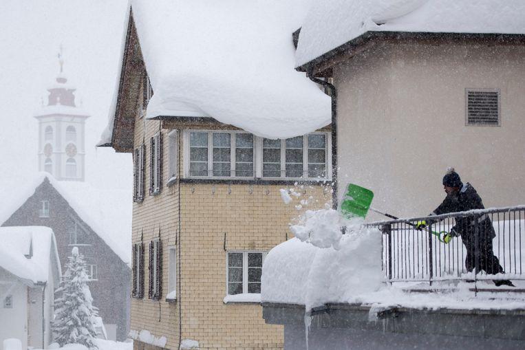Mensen proberen sneeuw weg te schuiven van een gebouw Beeld EPA