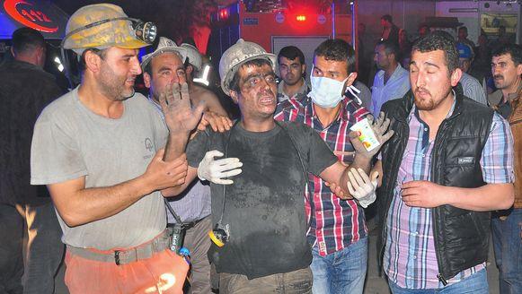 Een geredde mijnwerker wordt ondersteund door werkmakkers.