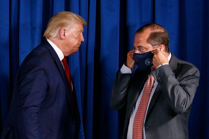 De Amerikaanse minister van Gezondheid Alex Azar (rechts met mondkapje) met president Donald Trump.