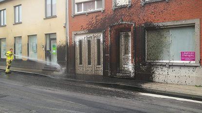 Mestkar spuit lading in het rond: straat, auto's en huizen besmeurd