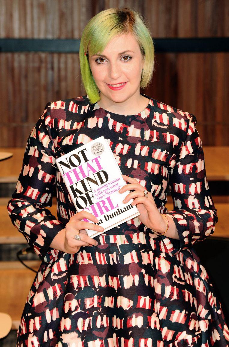 Lena Dunham met haar boek 'Not That Kind Of Girl'. Beeld getty