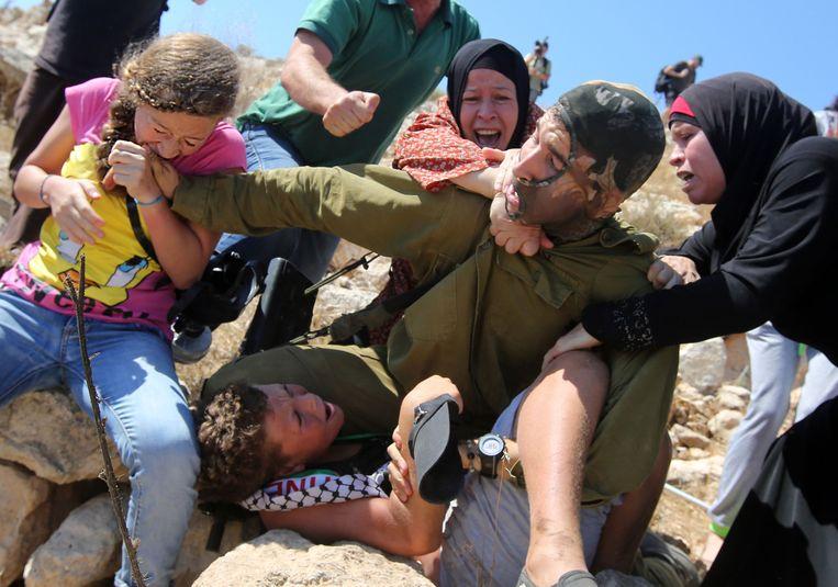 Jonge Palestijnse vrouwen proberen tegen te houden dat een Israëlische soldaat een jonge Palestijn aanhoudt. Tijdens rellen op de Westelijke Jordaanoever raakten Palestijnen slaags met het Israëlische leger, augustus 2015. Beeld AFP