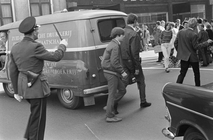 Twee demonstrerende jongeren worden op Prinsjesdag 1966 door de politie gemaand om snel door te lopen.