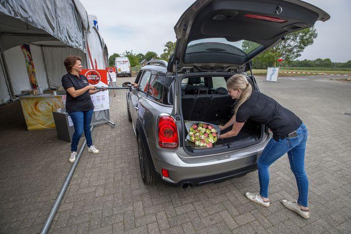 Carolien Keijsers laat de klant pinnen op afstand, terwijl dochter Tess een bos rozen in de achterbak van de auto legt.