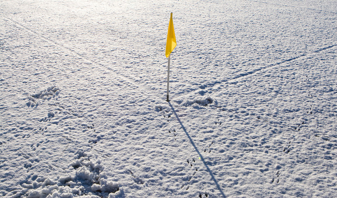 Een besneeuwd voetbalveld.