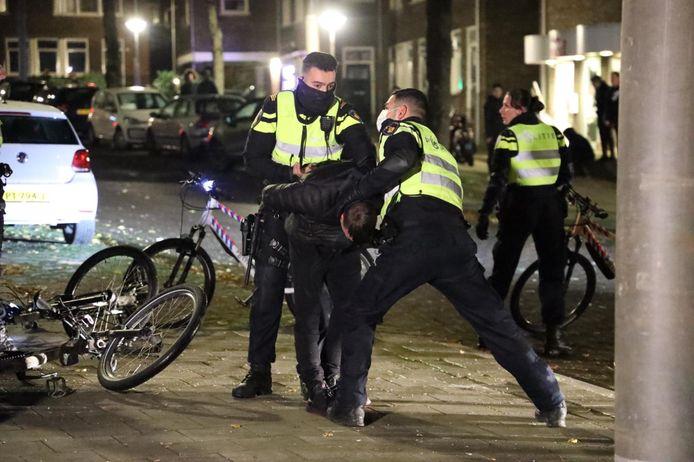 Politie-agenten houden een jonge oproerkraaier in bedwang in de Geitenkamp in Arnhem.