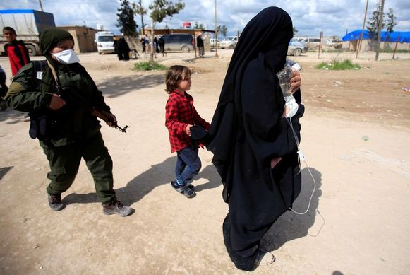 Een gevangen IS-weduwe met een infuus in het kamp al-Hol in noordoostelijk Syrië.
