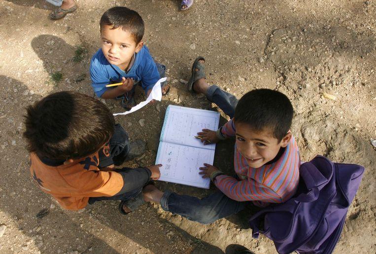 Jonge Syrische vluchtelingen doen hun huiswerk in een VN-vluchtelingenkamp in Libanon.