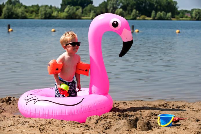 Olsen (2) vermaakt zich met water en zand bij de Haarrijnseplas. Voor het middaguur was het al behoorlijk druk op het strand.