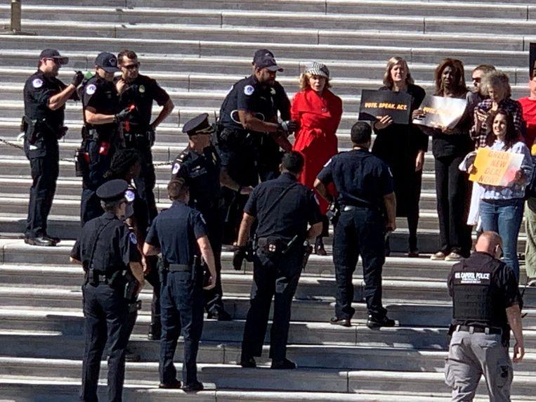 Jane Fonda (in rode jas) wordt gearresteerd