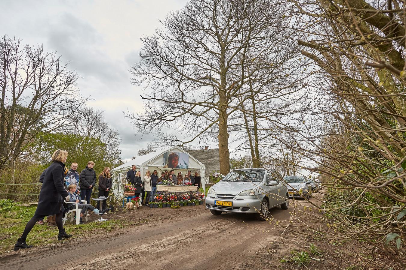 Vanuit de auto de laatste eer bewijzen aan Hans Imming, een mand langs het pad om bloemen of een kaart in te doen. Een uitvaart in tijden van corona.