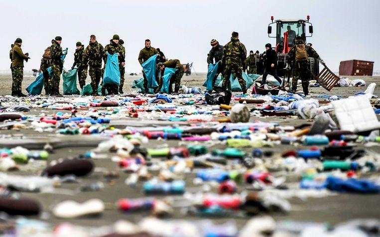 Militairen ruimen de spullen op die op het strand zijn aangespoeld nadat het vrachtschip MSC Zoe in januari 270 containers was verloren.  Beeld ANP