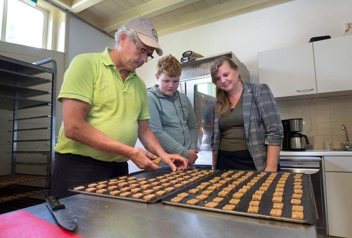 Moeder Rosi Gerritsen uit Utrecht en zoon Lars kijken toe hoe bakker Theo Hendriks van Koekfabriek Halsaf zijn werk doet.
