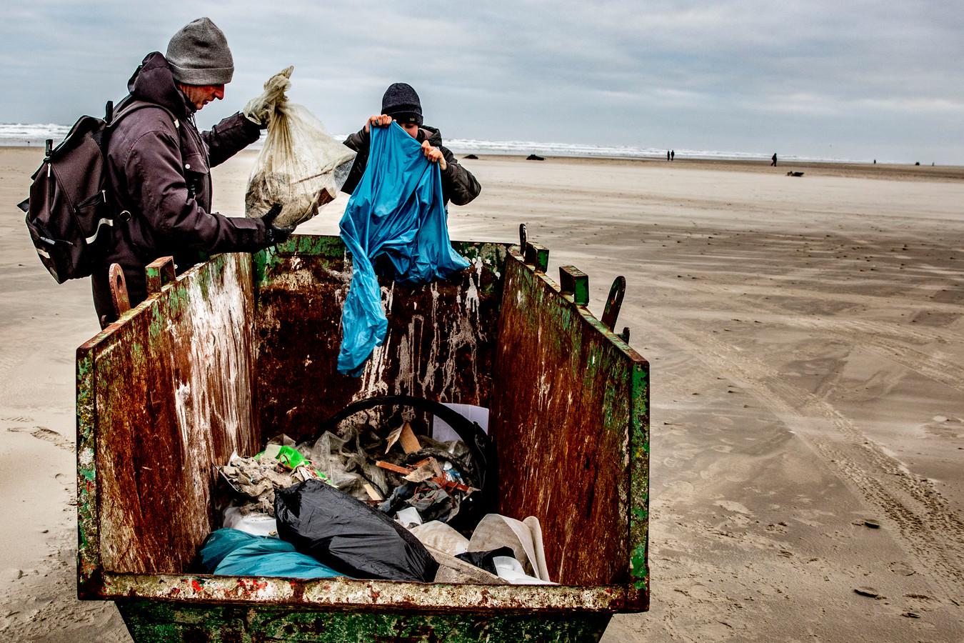 Vrijwilligers ruimen de spullen op die op het strand zijn aangespoeld nadat het vrachtschip MSC Zoe 270 containers was verloren.