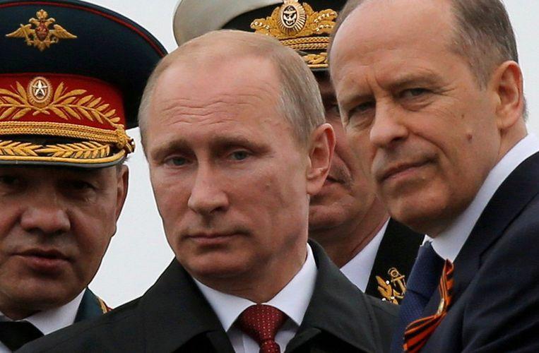 De Russische president Vladimir Poetin (C) met de chef van de Russische binnenlandse geheime dienst FSB, Alexander Bortnikov (R). (Archiefbeeld)