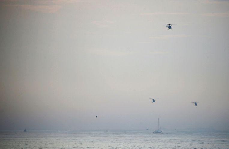 Begeleid door drie helikopters bereikt Franky Zapata (kleine stip boven zee) de Britse kust bij Dover. Beeld REUTERS