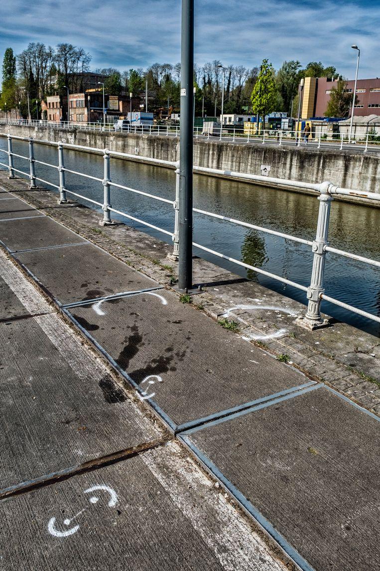 Witte markeringen getrokken door een verkeersexpert op het nog bebloede asfalt aan de Nijverheidskaai in Brussel moet de politie meer inzicht geven over het ongeluk.  Beeld Tim Dirven