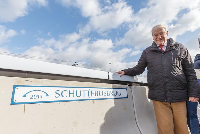Hans Schutte van het voormalige busbedrijf Schutte bij het naambordje van de brug.