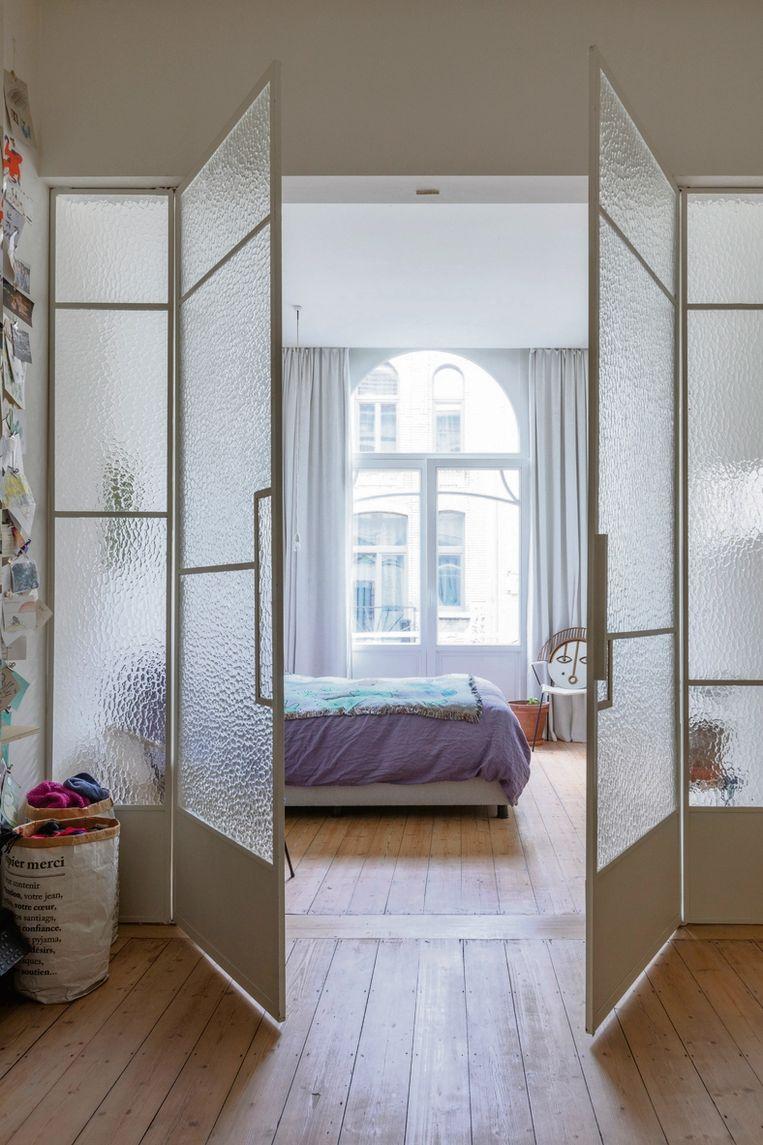 De witte stalen deur met kathedraalglas is een eigen ontwerp dat ze samen met een bevriende vakman maakten.