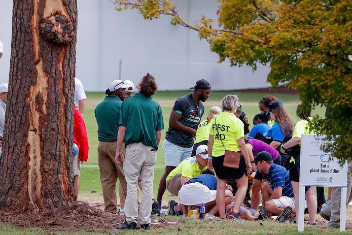 Hulpverleners bij een toeschouwer die is geraakt door boomstukken na het inslaan van de bliksem.