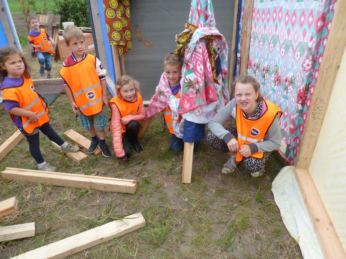 Leerlingen van kinderopvang Partou bij hun zelfgemaakte tent in het theatertje van kunstenaar/zanger/gitarist Jak Peters.