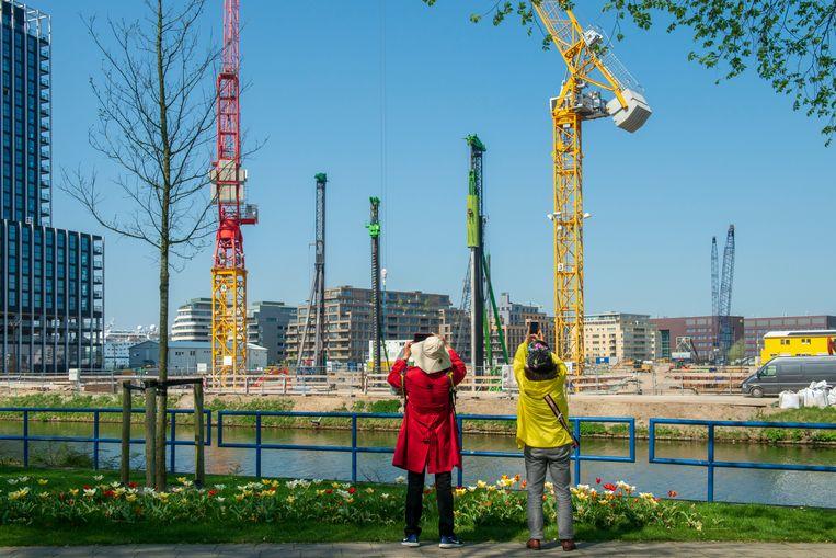 Toeristen in Amsterdam fotograferen een bouwput met hijskranen.  Beeld Hollandse Hoogte