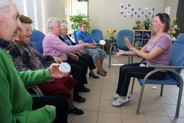 Senioren werpen doosjes naar coach Sabine.