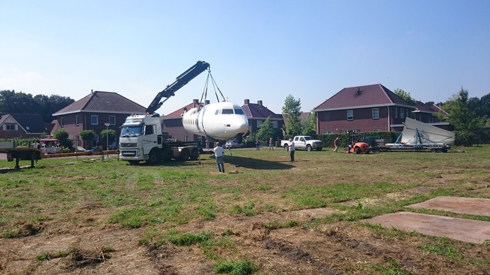 Vliegtuig wordt van de dieplader gehaald.