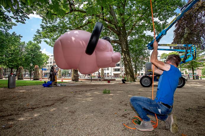 Het varken van kunstenaar Florentijn Hofman wordt tussen de bomen in het Jan Cunenpark omhoog gehesen.