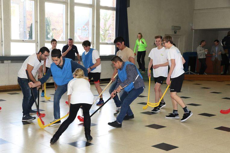 De leerlingen van de Heilige Familie en de asielzoekers spelen samen hockey.